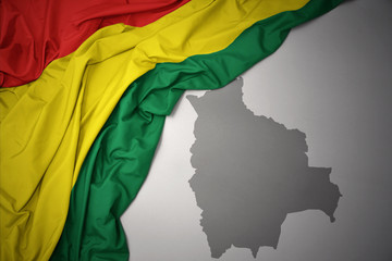 waving colorful national flag and map of bolivia.