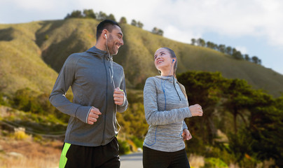 fitness, sport and technology concept - happy couple running and listening to music in earphones over big sur hills background in california