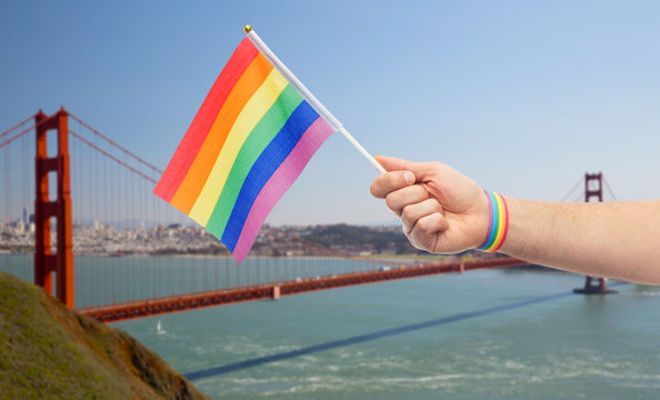 lgbt, same-sex relationships and homosexual concept - close up of male hand with gay pride awareness wristband holding rainbow flag over golden gate bridge in san francisco bay background
