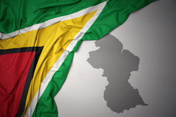 waving colorful national flag and map of guyana.