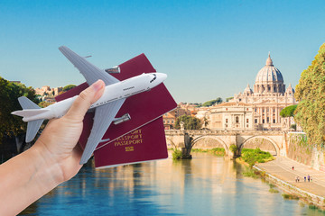 Plane travel concept, hand holding passports with plane against Rome cityscape