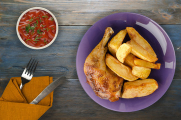 Chicken thigh with French fries on a wooden background.