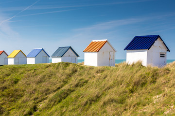 Colorful wooden beach cabins in the dunes, Gouville-sur-Mer, Normandy, France