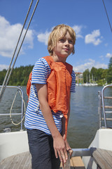 Child boy holding a yacht rudder. Cute boy captain on board of sailing yacht on summer cruise. Travel adventure, yachting with child on family vacation.