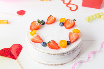 White birthday party background with healthy yougurt berry cake, bright party tools and decoration. Happy holiday design concept. Selective fous, copy space.
