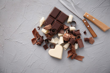 Pieces of chocolate with curls on light background