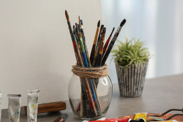 Set of paint brushes of professional artist on table in workshop