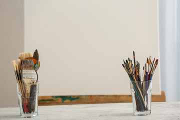 Set of tools with easel of professional artist on table in workshop