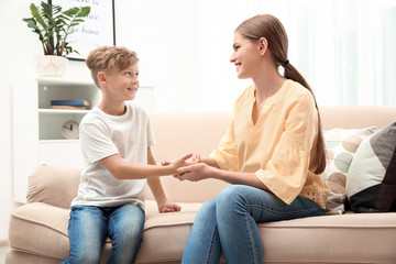 Young woman checking little boy's pulse indoors