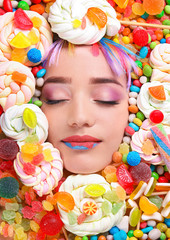 Face of beautiful young woman with creative makeup surrounded by different sweets