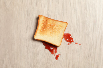 Overturned toast bread with jam on floor, top view
