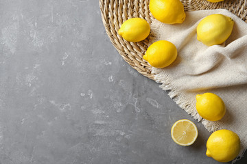 Flat lay composition with lemons, fabric and straw mat on gray background