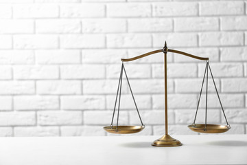 Scales of justice on table against brick wall. Law concept Wall mural