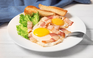 Fried eggs with bacon and toasted bread on plate served for breakfast
