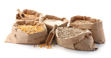 Paper bags with different types of grains and cereals on white background
