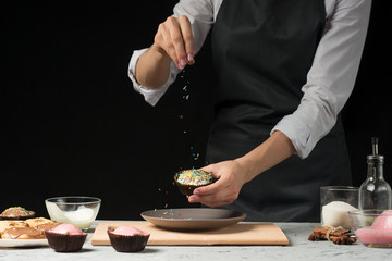 Chef prepares chocolate muffins on a dark background - fototapety na wymiar