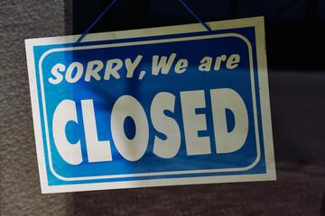 """Schild mit dem englischen Text: """"sorry, we are closed"""" hinter der Glasscheibe einer Shoptür"""