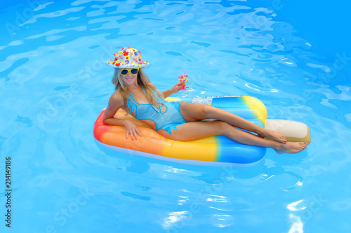 A young girl wearing a blue swim suit and a blue floral hat ...