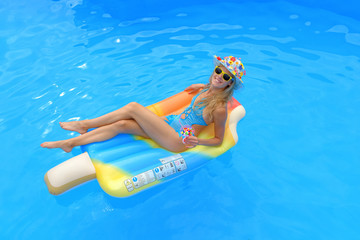 A young girl wearing a blue swim suit and a blue floral hat holds an imaginative cocktail drink in her hand. She  is lying on a swim ring in a swimming pool smiling at the camera.