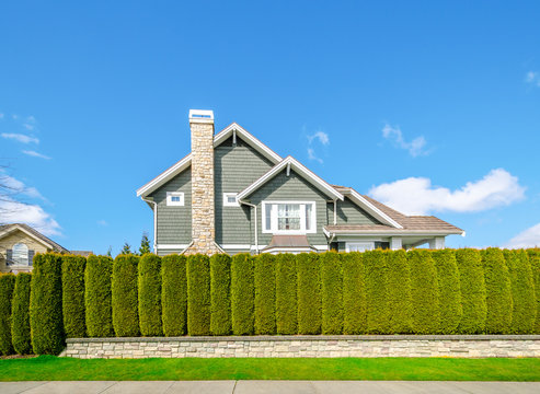 Beautiful house behind green hedge fence. Landscape trimming design. House exterior.