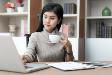 Young Asian businesswoman sitting in business office at desk, drinking coffee and using laptop. On table is laptop. businesswoman browsing internet, chatting, blogging her business.