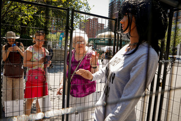 People look at a sculpture by artist Marilyn Miller that depicts a life-size immigrant mother and child separated by cages in New York