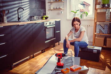 Worried woman renovating kitchen