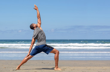 Athletic man at the beach in Reverse Warrior yoga pose