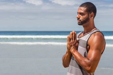 Athletic man at the beach in Prayer yoga position.
