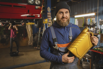 A bearded car mechanic works in the garage. Car mechanic in the garage. Hard work.