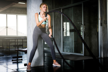 Young beautiful woman exercising with battle ropes at the gym.