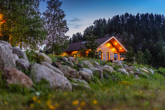 House in the forest. Cottage on the background of stones. Evening landscape with a house. The light burns in the houses.