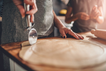 Mother and daughter cutting dough on wooden table