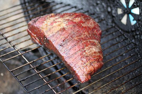 Dry rub beef brisket on the BBQ grill.
