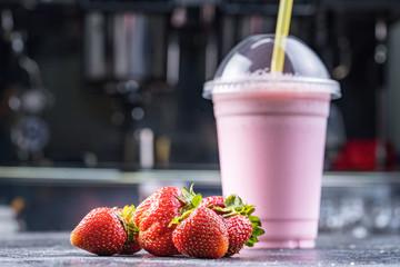 Strawberry milk shake to take away with straw on a dark background