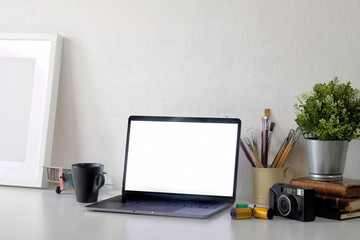Mockup blank screen laptop with poster on artist photographer desk. designer workspace with laptop and creative craft tools.