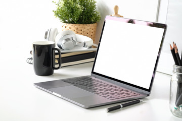 Workspace with blank screen laptop and office supplies.