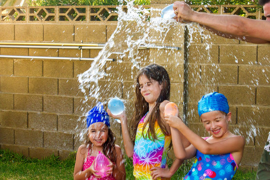 The Arms of a Father Break a Water Balloon Over the Heads of His Three Daughters