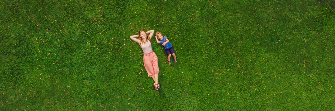Mom and son are lying on the grass in the park, photos from the drone, quadracopter BANNER long format