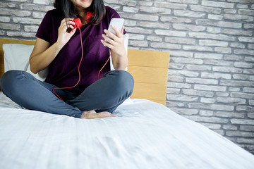 Young beautiful woman enjoying the music by tablet and relax on bed in bedroom. Relaxation concept.