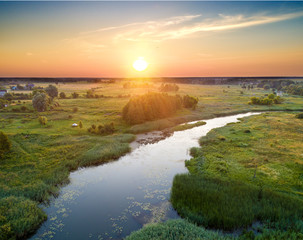 Sunrise in the countryside. River in a meadow. View from above