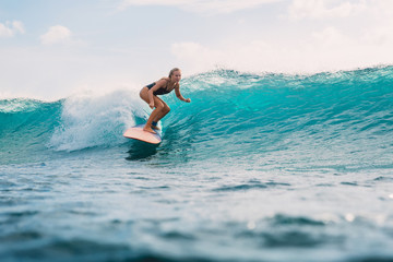 Surf woman on surfboard during surfing. Surfer and ocean wave