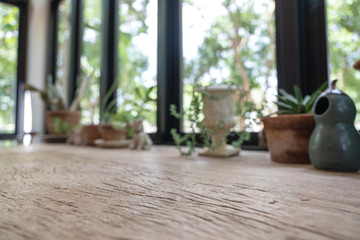 Closeup blur image of a wooden table with flowerpots in background