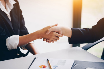 Businesswoman shaking hand for a complete business deal together successful, finishing up a meeting. Teamwork concept. Partnership concept and dealership concept.