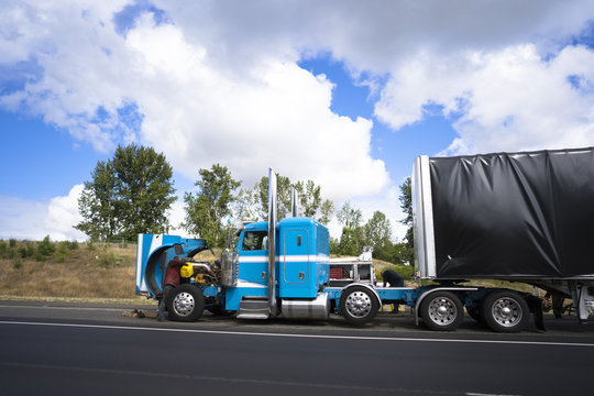 Truck drivers repairing big rig semi truck with open hood right on the road shoulder