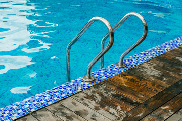 Bright blue swimming pool with stairs and wooden deck at hotel.
