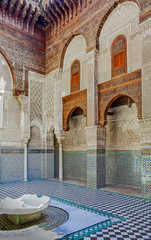 Ornate mosaic and carvings in a courtyard of a Moroccan medersa