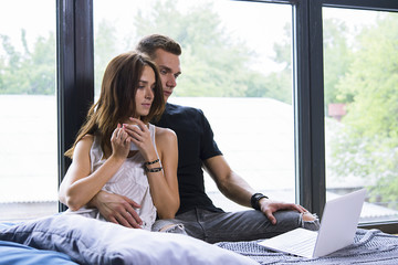 cute woman and man with a cup sitting near the window in the apartment, love