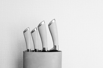 Set of metallic knives in holder in black and white