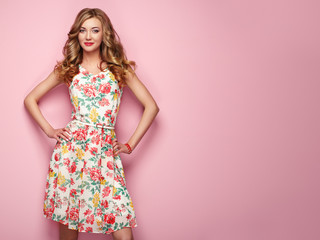 Blonde young woman in floral spring summer dress. Girl posing on a pink background. Summer floral outfit. Stylish wavy hairstyle. Fashion photo. Blonde lady Wall mural